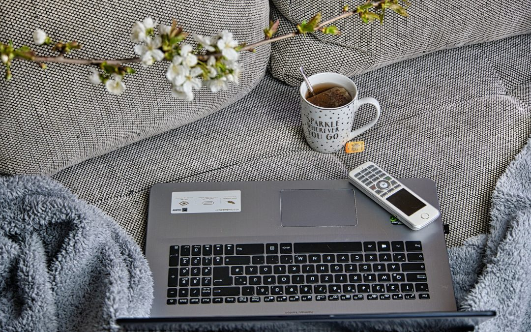 Working at home, laptop computer, phone, cup of coffee, blanket, all on the sofa